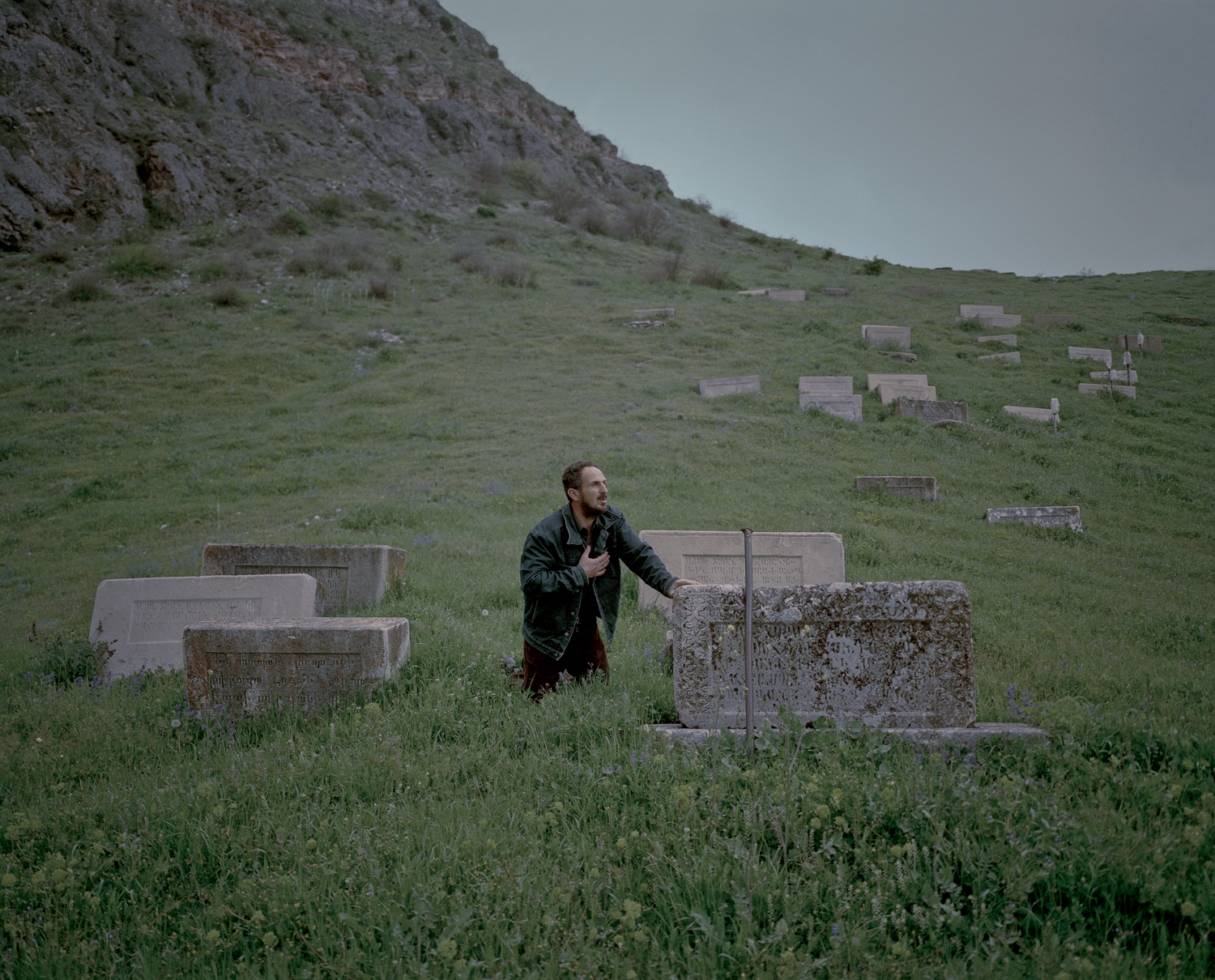 Vardadzor.  Hovik is praying among the Armenian gravesites.  He put the heavy headstones back onto the graves alone, with the help of metal rods and pullies.