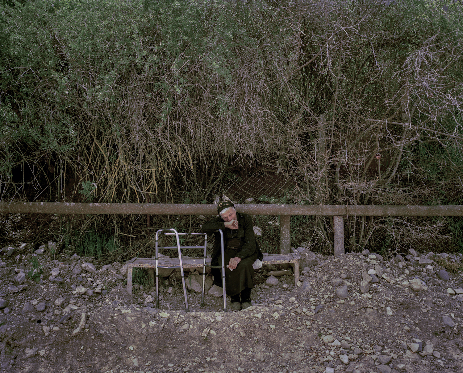 Vardadzor. Grieving widow crying on the bench in front of her/his house.